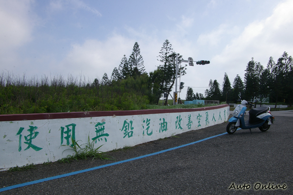 當著電動機車的面,牆壁上寫著:「使用無鉛汽油改善空氣人人有責」。